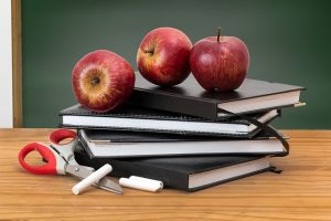 messy stack of teacher supplies, including books, chalk, and apples
