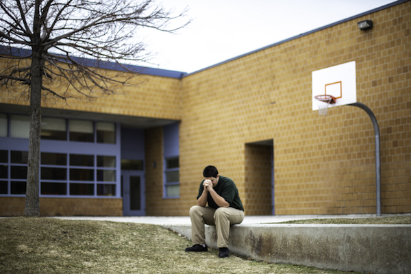 A student in Utah sits alone outside his classroom