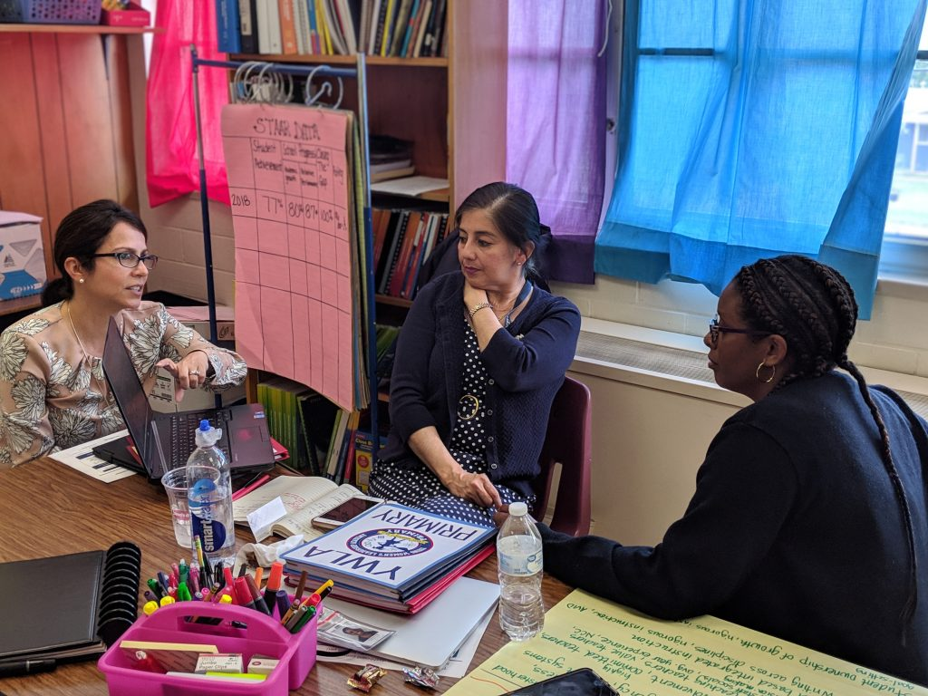 three women school leaders sit around a tale with colorful writing and markers