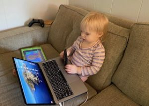 Toddler on a coach with a laptop, tablet, smartphone, and videogame controller