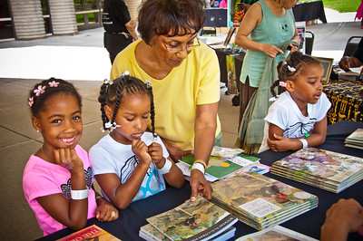 three young black girls and one black adult looking at a table of books, Knight Arts Challenge Detroit: Charles H. Wright Museum of African American History The Charles H. Wright will use the arts to foster an interest in reading by weaving interactive cultural experiences throughout the museum's Children's Book Fair.