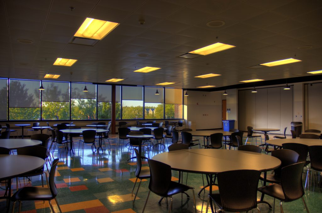 Monroe Community College Cafeteria, all seats at round tables empty, yellow overhead lighting